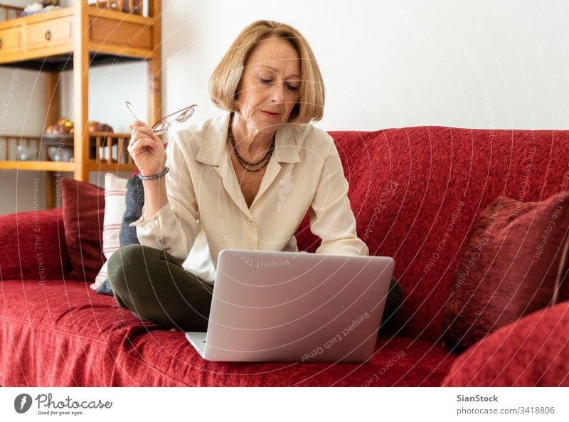 Elegante, reife Frau, die zu Hause einen Computer benutzt älter Dame gealtert Schönheit Wohlbefinden sorgenfrei Komfort attraktiv bequem lässig blond entspannt
