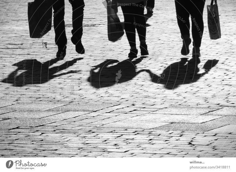 Schatten einer Menschengruppe - der flotte Dreier Beine einkaufen Einkaufstüte Stadtbummel Einkaufsbummel shoppen Pärchen 3 laufen Dreiergruppe Füße Straße