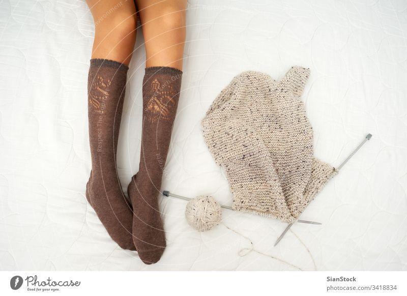 Foto einer Frau auf dem Bett mit Garn und Stricknadeln stricken Wolle Handwerk Nadel Pullover Muster Mode warm Bekleidung Schnur Hobby traditionell Material