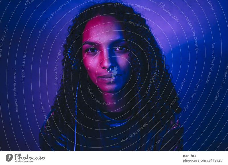 Künstlerisches Porträt mit Farblicht einer jungen Frau neonfarbig schwarz Kunst künstlerisch cool Afro-Look Afroamerikaner Musik Kopfhörer Headset