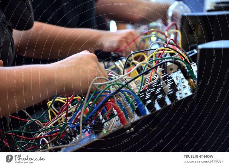DJ Equipment Electro Mischpult für elektronische Musik mit vielen Reglern, bunten Kabeln und Steckern wird von zwei Händen gerade gesteuert elektronische musik