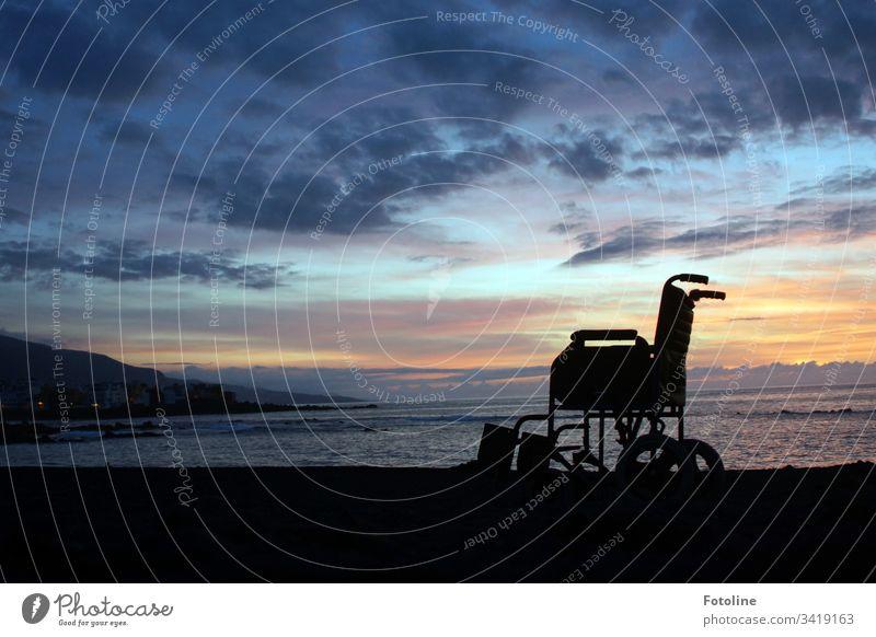 Rollstuhl am Strand von Puerto de la Cruz auf Teneriffa im Sonnenuntergang Berge u. Gebirge Landschaft Außenaufnahme Himmel Natur Farbfoto Menschenleer Wolken