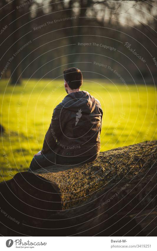 Mann sitzt alleine auf einem Baumstamm und genießt die Ruhe Mensch Natur ruhe abstand draußen einzeln Einzelgänger 1 Person eine person Herbst herbstlich