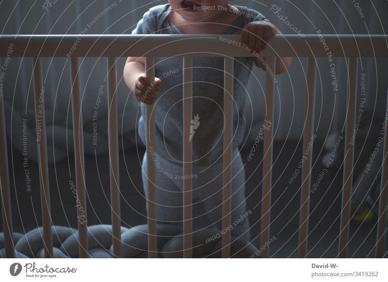 Kind im Kinderbett ist wach und weint schreit aufgewacht Kleinkind Baby Babybett schreien weinen Gitter eingesperrt emotionen emotional alleine einsam angst