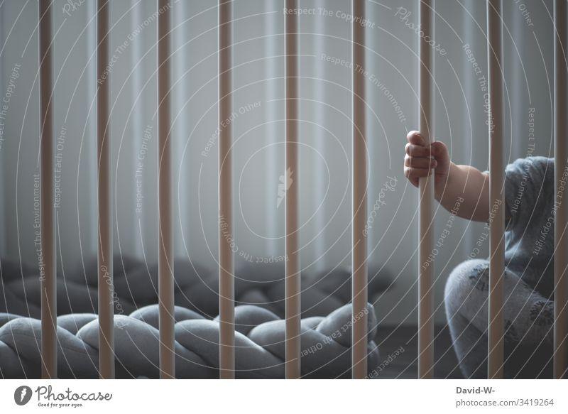 Baby hinter Gittern im Kinderbett Hand klein Junge Kleinkind schlafen wach eingesperrt niedlich festhalten süß alleine Einsam anonym greifen Erziehung