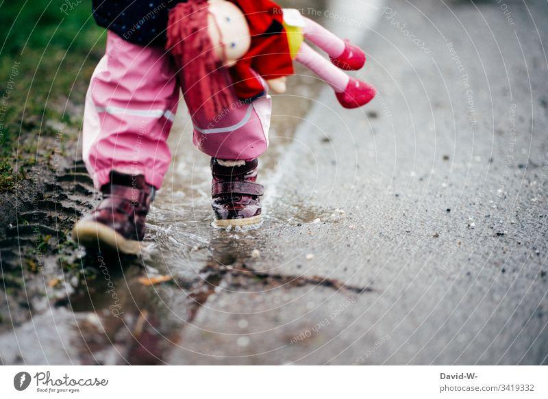 Mädchen Kind läuft mit Puppe durch Pfütze an einer Straße entlang nass gefährlich autoverkehr laufen unsicher Kleinkind Gefahr schlechtes Wetter Herbst