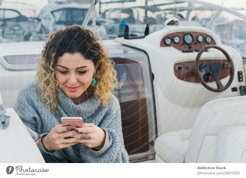 Zufriedene Dame mit Smartphone auf Yacht Frau benutzend Jacht Lächeln Browsen Handy Lachen zufrieden Inhalt genießen Surfen zuschauen Anschluss Gerät Apparatur