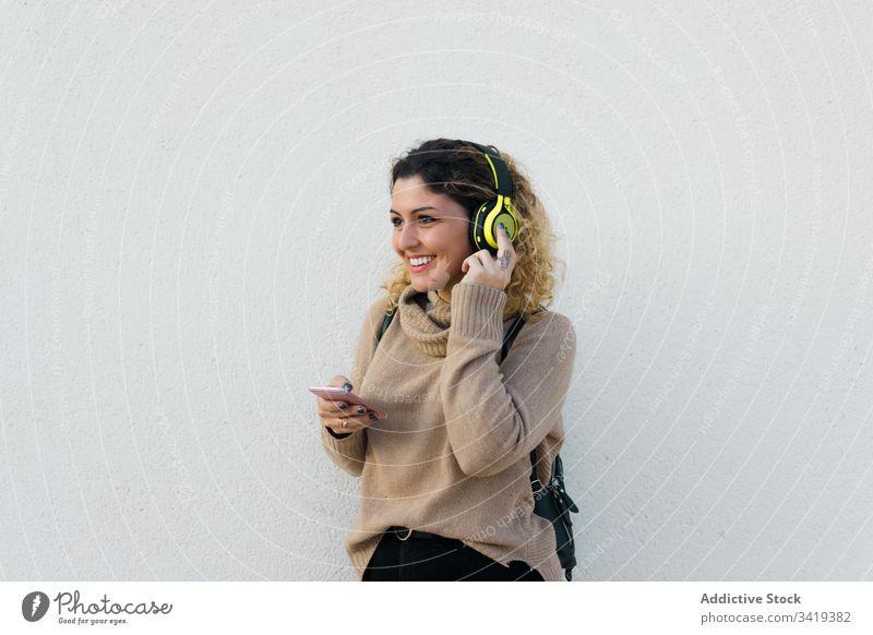Zufriedene Frau mit Kopfhörern und Smartphone benutzend Lächeln lässig Lachen genießen Inhalt zuhören Musik Gerät Apparatur modern Kommunizieren Anschluss