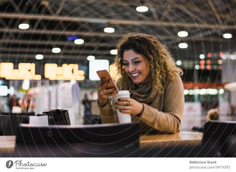 Frau beim Kaffeetrinken und am Mobiltelefon am Flughafen Smartphone Telefon Getränk Tasse lässig zum Mitnehmen Funktelefon modern sich[Akk] entspannen Pause