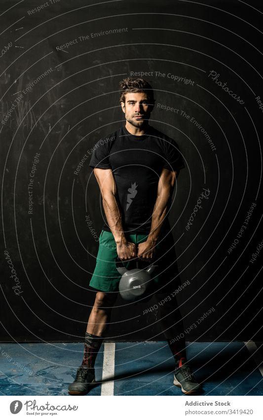 Muskelsportler mit Kettlebell im Fitnessstudio Sportler Gewichtheben operativ Training muskulös Gesundheit männlich Athlet Übung Kraft stark Körper passen