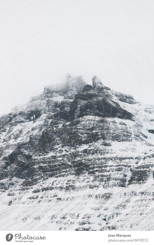 Schneeberg zwischen den Wolken Berge u. Gebirge schneebedeckter Berg Landschaft Schneelandschaft kalt Island Norden Nebel Natur vijes Tourismus Winter