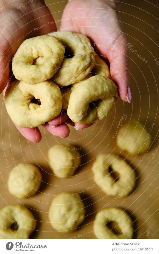 Nutzpflanzenweibchen machen Donuts aus Teig Frau Krapfen Koch Teigwaren Tisch Ring Form heimwärts Gebäck Lebensmittel frisch Snack Bäckerei Dessert süß Mahlzeit