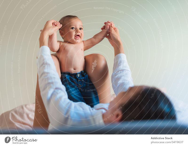 Glückliche gesichtslose Mutter spielt mit Baby im Schlafzimmer spielen Lächeln Lügen genießen Zusammensein Kind Eltern bezaubernd Liebe wenig Pflege unschuldig