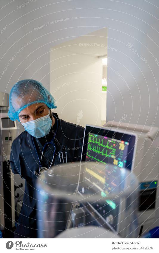 Nachdenklicher Erwachsener in Schutzmaske und Uniform in der Klinik Arzt Krankenhaus Medizin Mann medizinisch Chirurgie prüfen professionell männlich Mundschutz