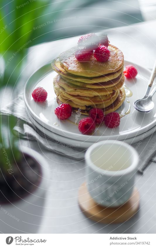 Teller mit Pfannkuchen auf dem Tisch während des Frühstücks Himbeeren Morgen Serviette Tasse Pflanze Topf heimwärts süß Lebensmittel Dessert lecker
