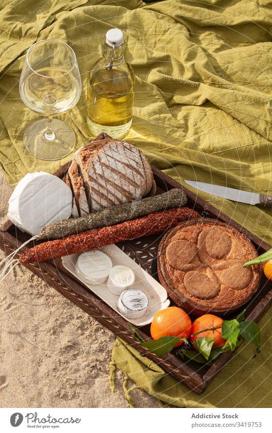 Gebäck und Mandarinen mit Käse und Würstchen in der Nähe von Wein während des Picknicks Lebensmittel Decke Strand Pasteten Brot Wurstwaren lecker geschmackvoll