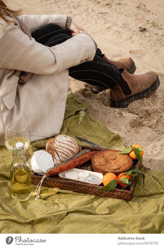 Erntehelferin sitzt neben Wein und Tablett mit Gebäck und Mandarinen mit Würstchen und Käse Frau Picknick Strand Lebensmittel Decke ruhen Sand sitzen Brot