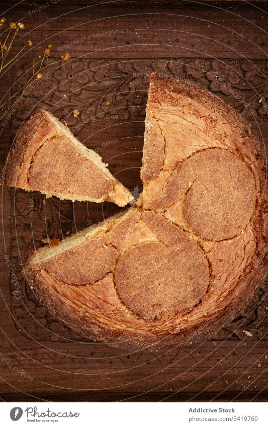 Torte mit abgeschnittenem Stück auf Holztisch Pasteten Tisch Spielfigur frisch Lebensmittel Ornament hölzern Blume lecker geschmackvoll Brot natürlich organisch