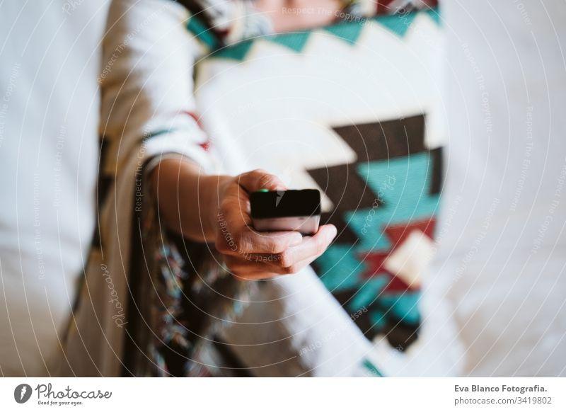 Nahaufnahme einer nicht erkennbaren Frau, die zu Hause die Fernbedienung des Fernsehers hält. Fernseh- und Technikkonzept abgelegen Kontrolle FERNSEHER