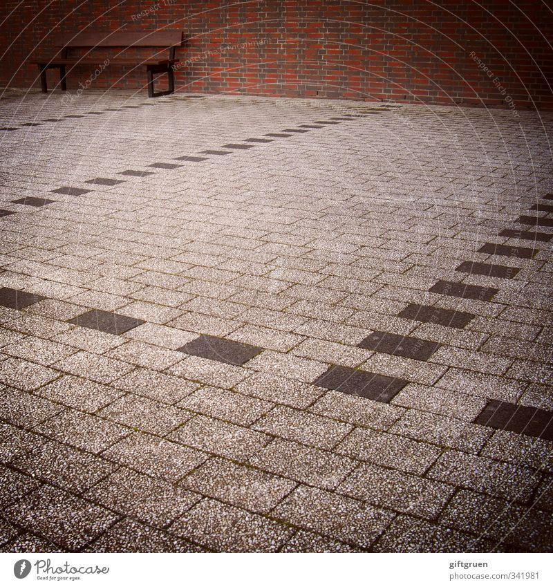 eingeparkt Mauer Wand sitzen Bank Sitzgelegenheit Parkplatz Backstein Steinboden Linie Strukturen & Formen Einsamkeit leer grau skurril parken Perspektive trist