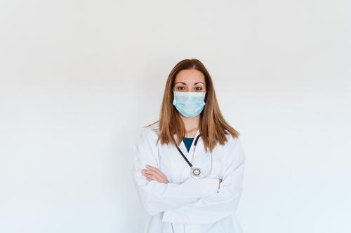 Porträt einer Ärztin, die im Haus eine Schutzmaske und Handschuhe trägt. Konzept des Coronavirus Frau Arzt professionell Corona-Virus Krankenhaus arbeiten
