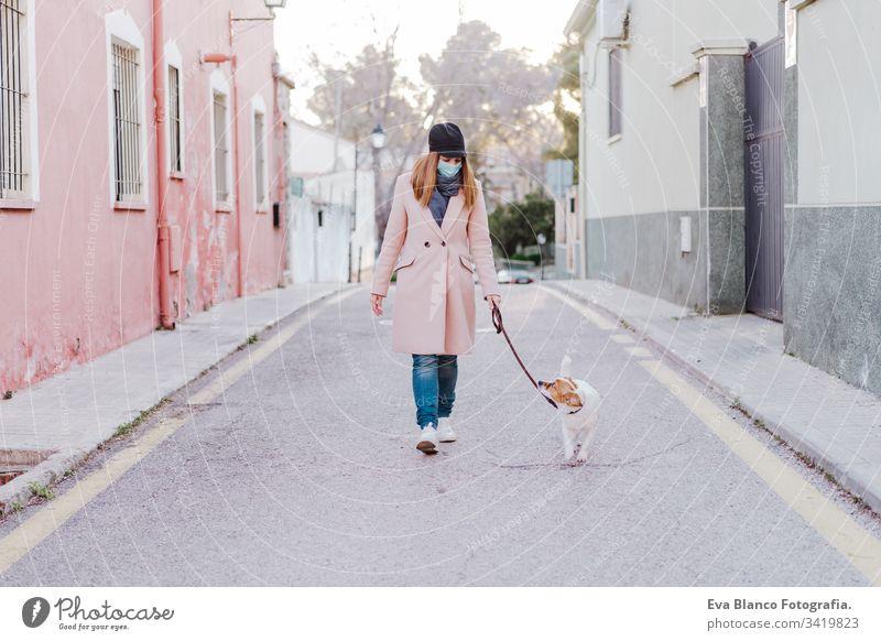 Weiße Frau auf der Straße mit Schutzmaske und mit ihrem Hund spazieren. Mundschutz Corona-Virus im Freien Handy Technik & Technologie Internet Kaukasier