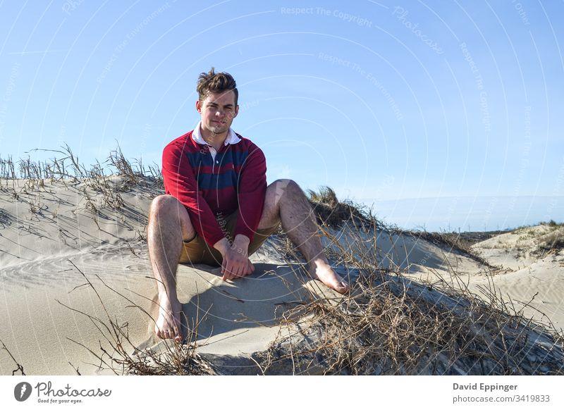 Typ im rot-blauen Rugby-Hemd auf Sanddünen sitzend Strand Stranddüne Ferien & Urlaub & Reisen Küste Düne Meer Erholung
