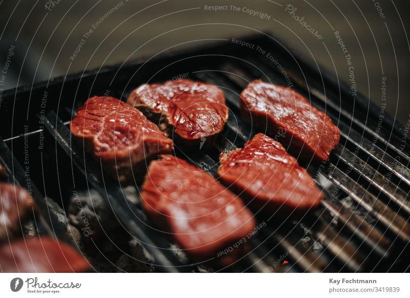 rohes Fleisch auf einem Grillrost Barbecue Barbecue-Grill Grillen grillen Rindfleisch Blut Essen zubereiten Abendessen Lebensmittel Raster gegrillt erwärmen
