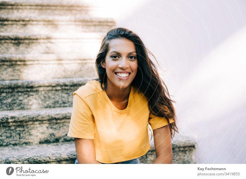 lateinamerikanisches Mädchen, das auf der Treppe sitzt und lächelt 20s Erwachsener attraktiv schön Schönheit Brasilien brünett sorgenfrei lässig heiter