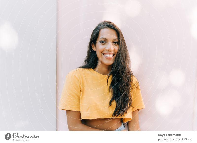 lateinamerikanische Frau lächelt vor weißem Hintergrund 20s Erwachsener attraktiv schön Schönheit Brasilien brünett sorgenfrei lässig heiter Selbstvertrauen