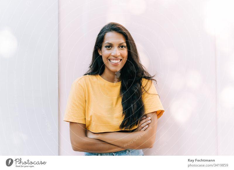 lateinamerikanisches Mädchen lächelt vor weißem Hintergrund 20s Erwachsener die Arme verschränkt attraktiv schön Schönheit Brasilien brünett sorgenfrei lässig