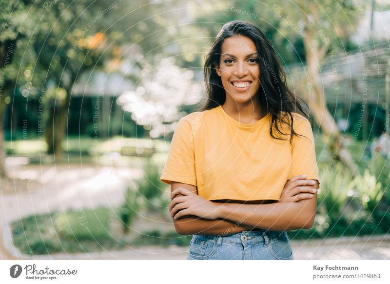 Bild eines lächelnden lateinamerikanischen Mädchens 20s Erwachsener die Arme verschränkt attraktiv schön Schönheit Brasilien brünett sorgenfrei lässig heiter