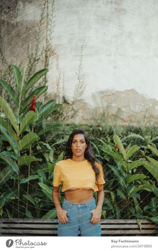 Brasilianerin steht selbstbewusst vor Wand jung jugend Jeanshose Selbstvertrauen urban sexy Fitness gelb elegant Bräune lateinamerikanisch stylisch Dame