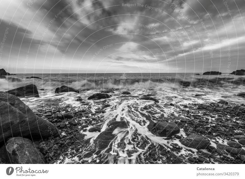 Wellen brechen und spülen die Kiesel am Strand, Wolken ziehen vorbei, der Blick wandert zum Horizont Kieselsteine Brandung Meer nass Steine Himmel Natur Küste