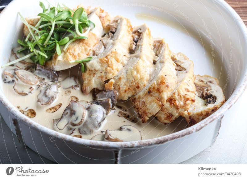 Hähnchenbrust-Rolle mit Champignons. Neben der Champignon-Sauce. Auf dunklem Hintergrund. Mit Mikrogrün dekoriert. Lebensmittel Fleisch Ostern Abendessen