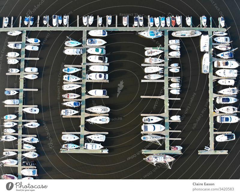 Luftaufnahme vieler Boote, die in einem Yachthafen anlegen, gegen dunkles Wasser, erstellt mit einer Dji-Kamera. Jachthafen Segeln Decks Küstenstreifen Seeküste