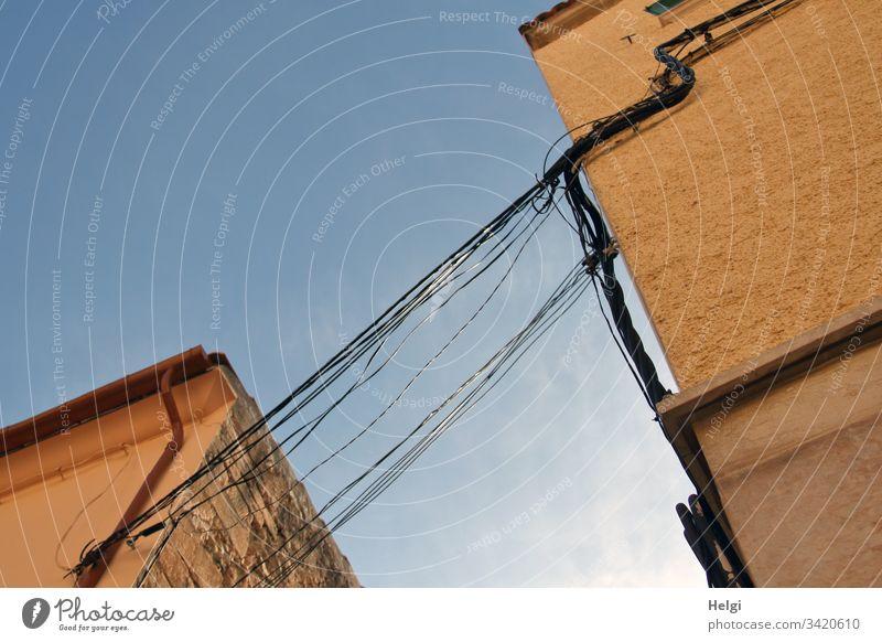 viele Stromkabel verlaufen unter freiem Himmel von einem Gebäude zum anderen Energieversorgung Stromversorgung Kabel Elektrizität Technik & Technologie
