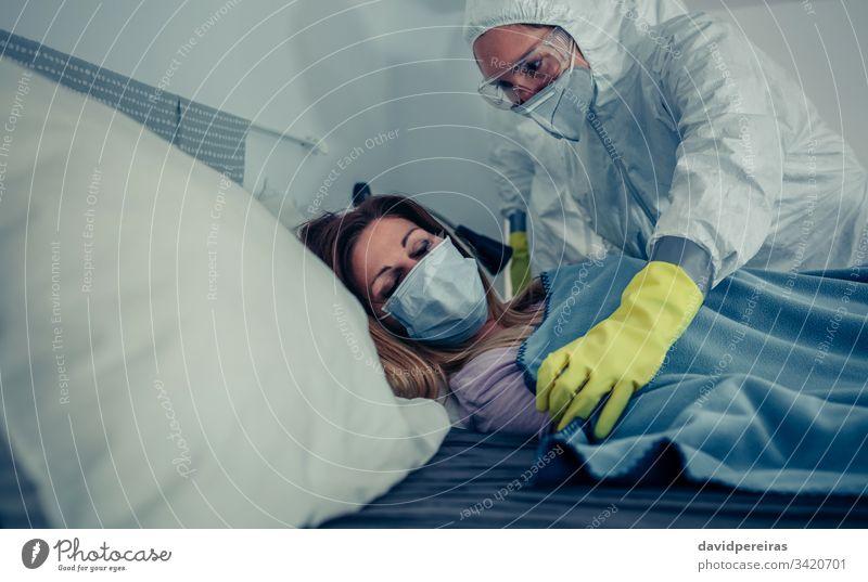 Frau in Hausquarantäne wegen eines Virus in ärztlicher Behandlung krank Coronavirus schützende Gesichtsmasken Seuche bakteriologischer Schutzanzug Pflege