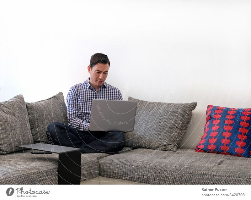 Mann arbeitet von zu Hause aus mit einem Laptop im Wohnzimmer Erwachsener lässig Computer Textfreiraum Unternehmer Freiberufler heimwärts Heimarbeitsplatz