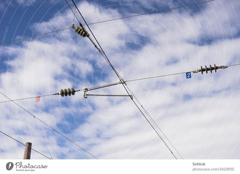 Schornstein und Oberleitungen mit Glasisolatoren und Nummern vor blauem Himmel mit Wolken Stromtransport Elektrizität Isolator Schilder Zahlen Schornsteinkopf 1