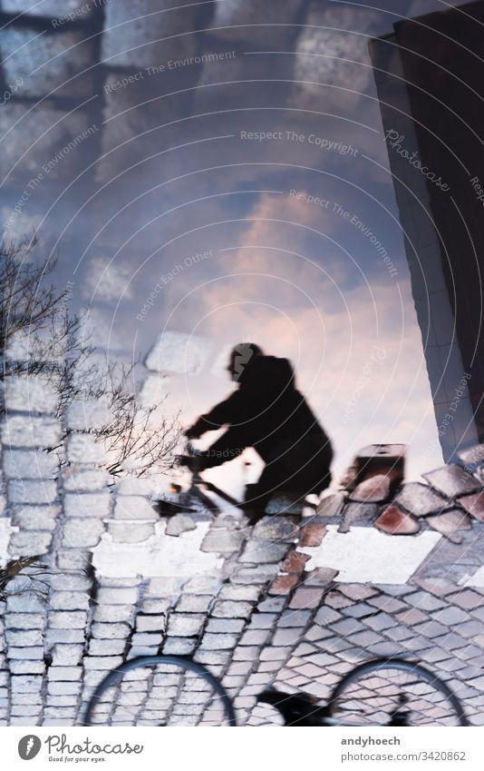 Radfahrerreflexion von unten nach oben abstrakt Kunst Hintergrund Fahrrad Radfahren Gesäß Gebäude Großstadt Wolken Kopfsteinpflaster Collage Konzept verwirrt