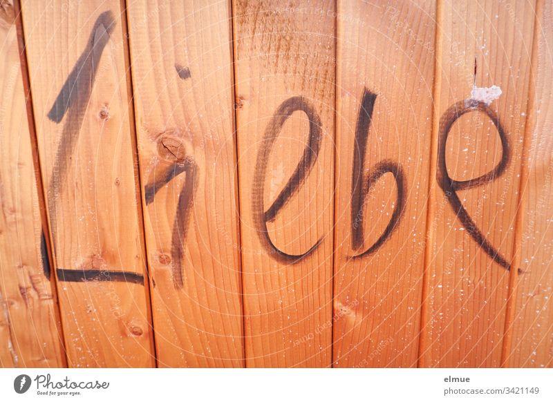 """Wort """"Liebe"""" an eine hellbraune Holzwand geschrieben Buchstabe schreiben Schmiererei Liebesbezeugung Mitteilung verliebt Schriftzeichen Information"""
