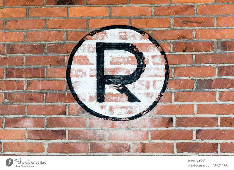 Großes schwarzes R auf weißem Grund an einer Backsteinmauer Buchstaben Farbfoto Tag Schriftzeichen Außenaufnahme Großbuchstabe Schild Ziegelmauer Gebäude
