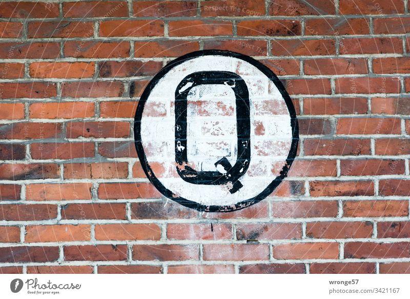 Großes schwarzes Q auf weißem Grund an einer Backsteinmauer Buchstaben Farbfoto Tag Schriftzeichen Außenaufnahme Großbuchstabe Schild Ziegelmauer Gebäude