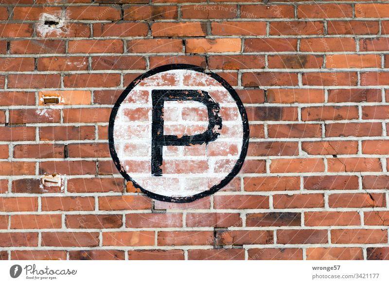 Großes schwarzes P auf weißem Grund an einer Backsteinmauer Buchstaben Farbfoto Tag Schriftzeichen Außenaufnahme Großbuchstabe Schild Ziegelmauer Gebäude