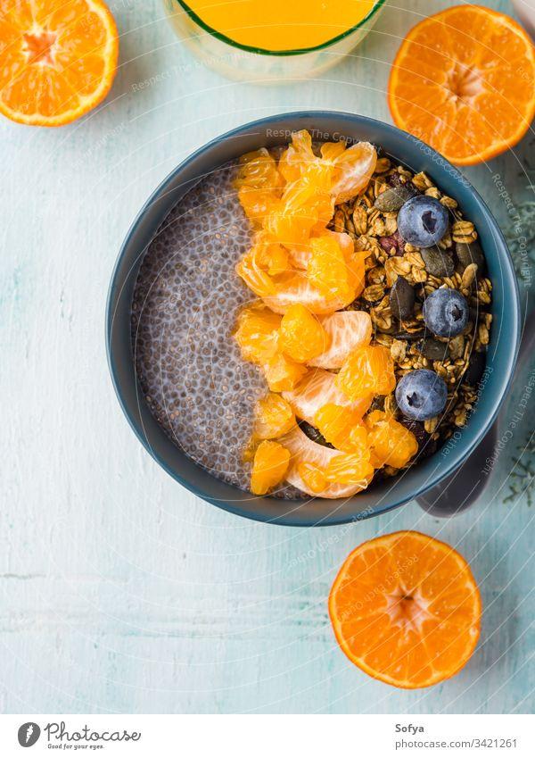 Chia-Pudding mit Mandarinen und Granola Chiapudding Müsli Schalen & Schüsseln Pastell türkis Matcha Tee hölzern Hintergrund Blaubeeren Frühstück Chiasamen