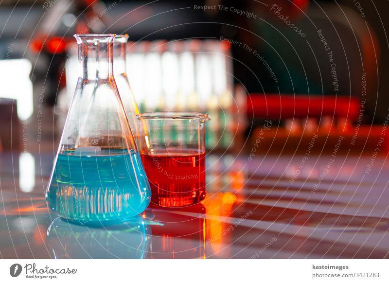 Beleuchteter Laborkolben mit farbigen chemischen Lösungen mit Schatten auf dem Tisch. Labor, Wissenschaft, Forschung, Chemie... konsept. Glaswaren Reagenzglas