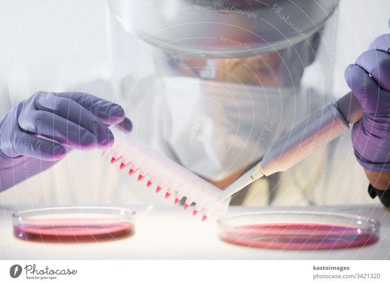 Wissenschaftlerin, die im Labor für die Entwicklung von Koronaviren-Impfstoffen forscht, mit einem Höchstmaß an Schutzausrüstung. Corona-Virus forschen covid-19