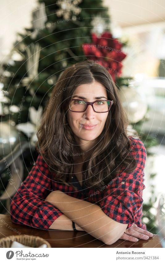 Hübsche Frau mit Brille, Porträt mit Weihnachtsbaum im Hintergrund Frauenporträt heimwärts Weihnachten 30s 40s attraktiv Kaukasier Spanisch eine Person