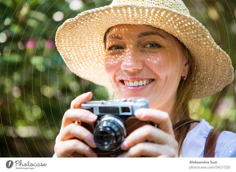 Nahaufnahme einer schönen Frau mit Strohhut, die im Tropenwald reist und mit einer Retro-Kamera fotografiert. Leichte Schatten durch die ausgeschnittene, detaillierte Krempe im Gesicht. Tourist mit Rucksack.